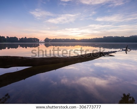 Beautiful sunrise over lake. Summertime tranquil landscape.