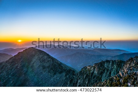 Man Sitting On Edge Mountain Looking Stock Photo - This man hikes up the transylvanian mountains every morning to photograph sunrise