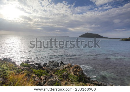 Beautiful Sunrise Over The Caribbean Sea With Islands, Clouds, Blue Skies, Clear Blue Water, And Rocky Shores. - stock photo