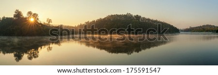 Beautiful sunrise over the forest lake with reflections