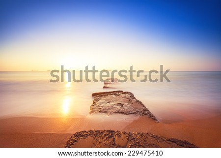 Beautiful sunrise over the horizon and foggy waves - stock photo