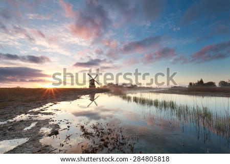 beautiful sunrise over windmill and river, Netherlands - stock photo