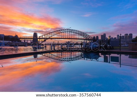 Beautiful sunrise scene at Sydney Harbour Bridge with dramatic sky colour and reflection - stock photo