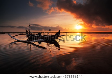 "Beautiful Sunrise Scene in Bali, Indonesia. The rowboat or ""Jukung"" is widely use as fishing boat by the local fisherman - stock photo"
