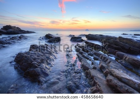 Beautiful sunrise scenery of a rocky beach in northern Taiwan, with reflections of golden sunlight on sea water and a distant island on horizon under dramatic dawning sky (Long Exposure Effect) - stock photo