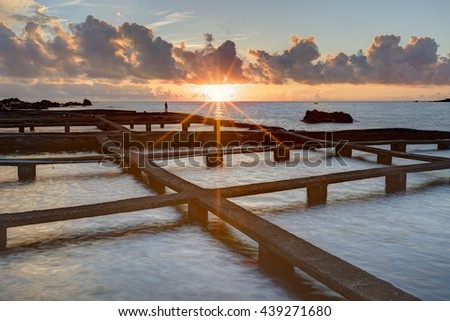Beautiful sunrise scenery of a sea ranch (fish farming) in northern Taiwan with peculiar artificial structures of aquaculture fishery & the rising sun on the distant horizon under dramatic dawning sky - stock photo