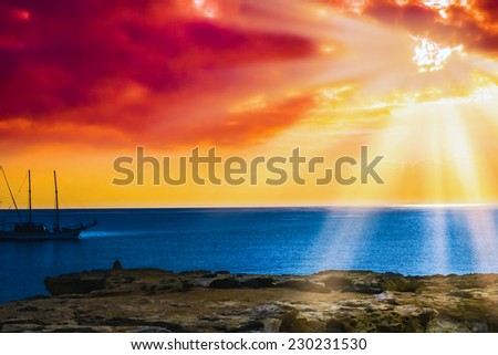 beautiful sunrise sun in the clouds on a quiet calm sea - stock photo