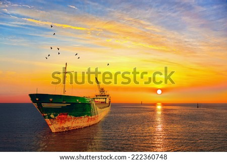 Beautiful sunrise with a dry cargo ship at sea.  - stock photo