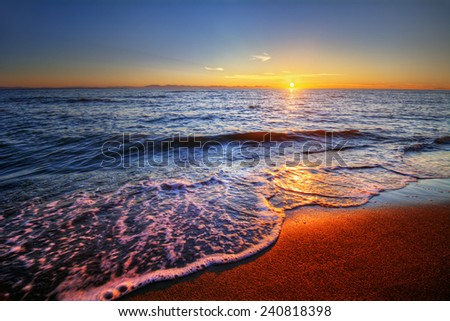 Beautiful sunrise with ocean sea-foam breaking on a sandy beach shore - stock photo