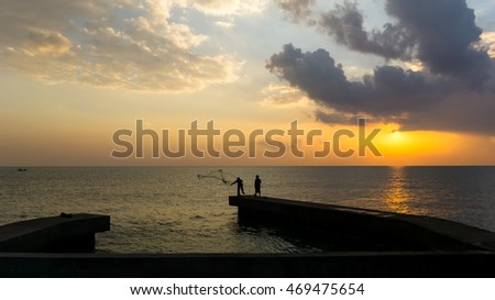 beautiful sunrise with silhouette of fisherman