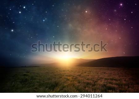 Beautiful sunrise with stars and galaxy in night sky. - stock photo