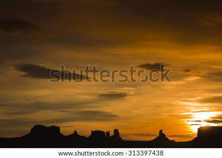 Beautiful sunrise with the silhluette of Monument Valley and its geological formations against an orange cloudy sky. USA 2012 - stock photo