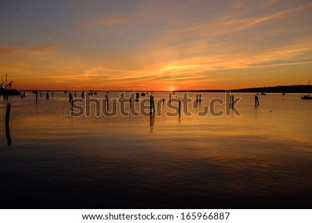 Beautiful sunrise with wood pilings in the bay waters of Rockland Harbor in Maine