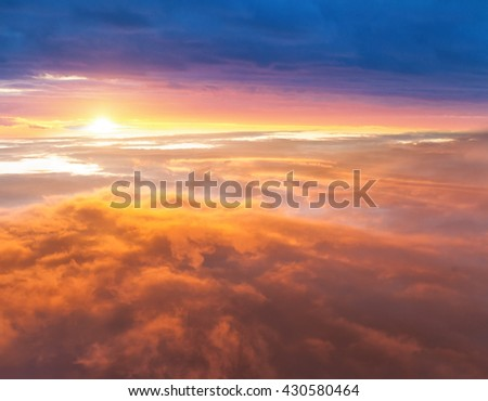 Beautiful sunset above clouds from airplane perspective - stock photo