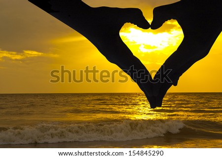 Beautiful sunset above the sea, and hands whit love signal - stock photo
