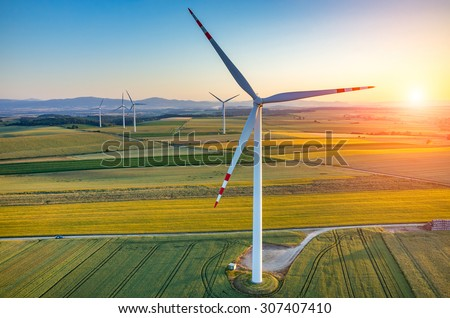 Beautiful sunset above the windmills on the field - stock photo