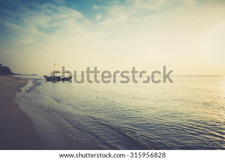 Beautiful sunset and beach with fishing boat - Dark tone color - stock photo