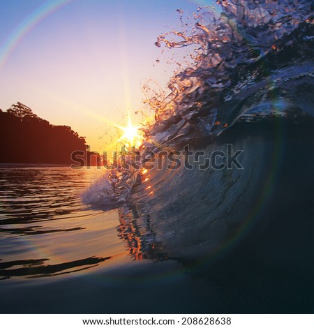 Beautiful sunset and breaking glossy ocean wave - stock photo