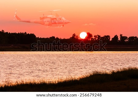 beautiful sunset and Double exposure of helicopter at river - stock photo