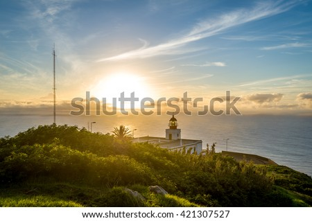 Beautiful sunset and lighthouse view to Atlantic ocean against the sun. Ponta do Pargo, Madeira island, Portugal