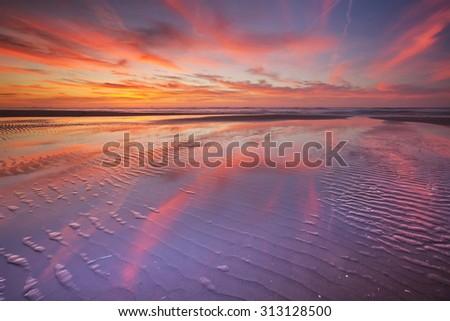 Beautiful sunset and reflections on the beach at low tide. - stock photo