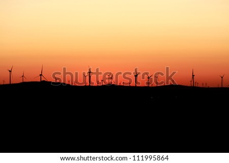 Beautiful sunset and wind turbines - stock photo