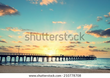 Beautiful sunset at Grange Jetty Adelaide Australia with peoples silhouettes  - stock photo