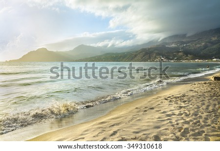 Beautiful sunset at Plakias village beach.Picturesque clouds shrouded the mountains and warm rays of light playing in the reflection of the Mediterranean sea.Panoramic view.Crete island.Europe. - stock photo