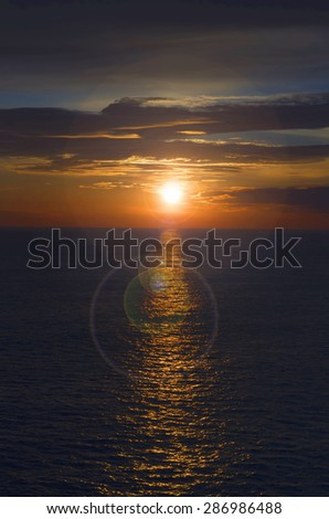 Beautiful sunset at sea with a lens flare effect - stock photo