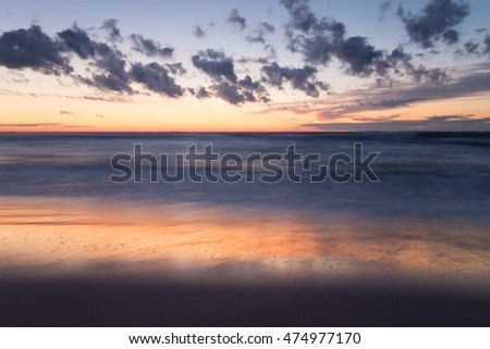 Beautiful sunset at the beach after a summers day, reflections in the water