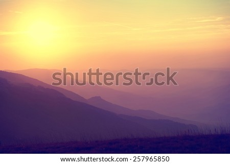 Beautiful sunset at the mountains. Colorful landscape with sun and orange sky. Colorized like instagram - stock photo