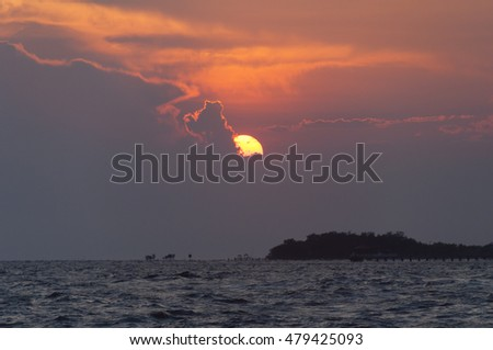 Beautiful sunset at the sea with dark light, subject is blurred and low key
