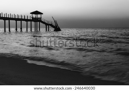 Beautiful sunset at tropical beach with jetty in black and white - stock photo