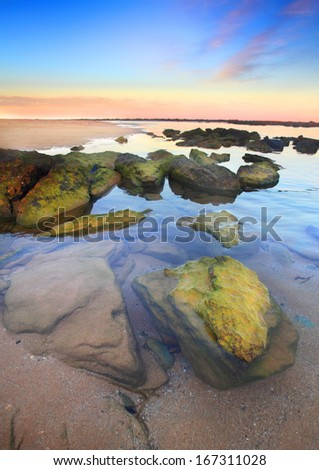 Beautiful sunset at unspoilt Toowoon Bay beach at low tide exposing the mossy green rocks on the reef shelf.  Australia.  Focus to foreground  - stock photo