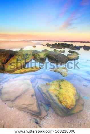 Beautiful sunset at unspoilt Toowoon Bay beach at low tide exposing the mossy green rocks on the reef shelf.  Australia.  Focus to foreground only