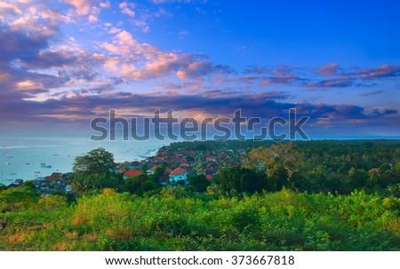 Beautiful sunset at village on island Lombongan near Bali - stock photo