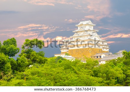 Beautiful sunset behind recently renovated Himeji-jo castle over the tops of trees seen from a distance in Himeji, Japan after 2015 renovations finished
