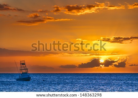 Beautiful sunset behind sport fishing boat with a flying bridge on Maui, Hawaii, USA - stock photo
