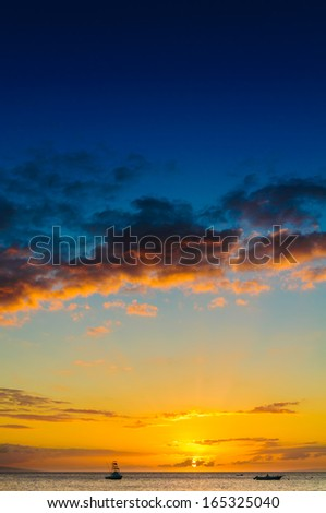 Beautiful sunset behind sport fishing boat with a flying bridge on Maui, Hawaii, USA - stock photo