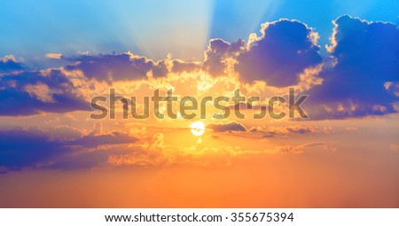 Beautiful sunset. Colorful sky with bright sun and cumulus clouds. - stock photo