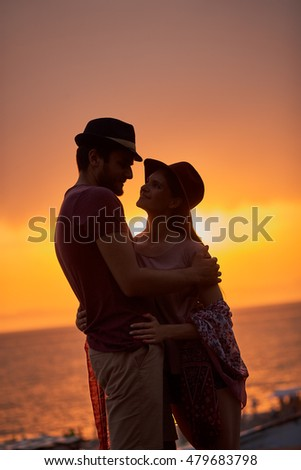 Beautiful sunset. Couple standing over sunset and sea background. Hugging each other.