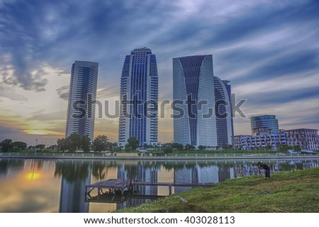 beautiful sunset during blue hour at Putrajaya Lakeside, Malaysia. hotel and building reflection on the lake. old jetty. soft and dramatic cloud