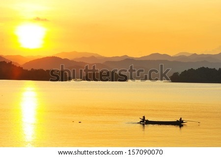 Beautiful sunset in Asia with a river and a boat on it