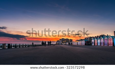 Beautiful sunset in Brighton, UK. Row of beach huts of Hove, vintage effect filter style