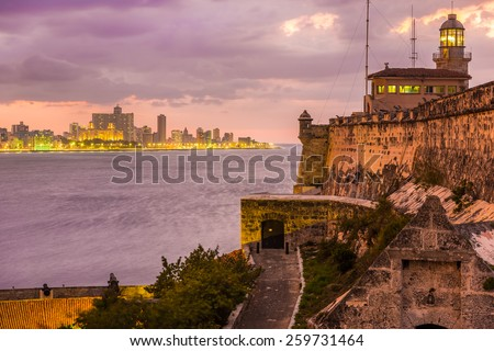 Beautiful sunset in Havana with El Morro lighthouse illuminated on the foreground - stock photo