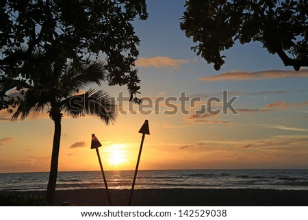 Beautiful sunset in Hawaii with Tiki Torches burning - stock photo