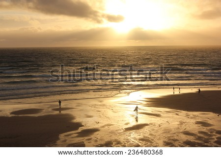 Beautiful sunset in Lacanau Ocean Beach with surfers and walkers, Gironde near Bordeaux, France