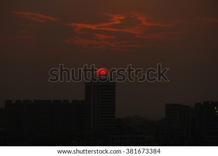 Beautiful sunset in the evening. The flare of the sun under black cloud. Wonderful cloudscape and wonderful landscape.   - stock photo