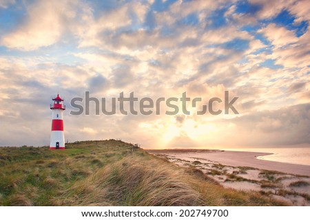 beautiful sunset landscape at the North sea with a lightning lighthouse, the Island of Sylt, Germany - stock photo