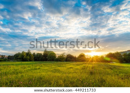 Beautiful sunset landscape over a meadow in evening - colorful sunlight wallpaper